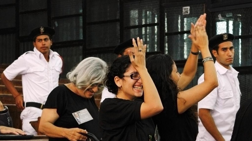 Prominent Egyptian blogger Alaa Abdel-Fattah's mother, Laila Soueif, a university professor who is an also an activist, background left, his sister Mona Seif, wearing eyeglasses at center, and his wife, Manal Bahy Eddin Hassan at right, cheer after his release on bail at a courtroom in Cairo, Egypt, Monday, Sept. 15, 2014. Relatives say that Egypt's most prominent activist who is standing retrial after being sentenced to 15 years in prison for violating to the country's draconian protest law, has been released on bail. (AP Photo/Ravy Shaker, El Shorouk) EGYPT OUT