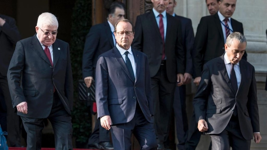 French President Francois Hollande, center, walks beside Iraqi President Fouad Massoum, left,  after the opening of the International conference intended to come up with an international strategy against  Islamic State extremists, in Paris, Monday, Sept. 15, 2014. As diplomats from around the world sought a global strategy to fight Islamic State extremists, Iran ruled out working with any international coalition, saying it had rejected American requests for cooperation against the militants. Man at right is undidentified.  (AP Photo/Brendan Smialowski; Pool)