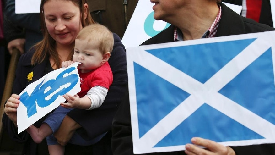 "In this image taken  Tuesday Sept.  9, 2014 six month old Caitlin Tierney chews a YES banner  is held by her mother Emma Connell  as Scottish First Minister Alex Salmond meets with Scots and other European citizens to celebrate European citizenship and ""Scotland's continued EU membership with a Yes vote"" at  Parliament Square in Edinburgh.   Across Scotland, dinner table talk is getting heated as families fight over how to vote in Scotland's independence referendum. A generation gap has opened up, with younger voters more inclined to back independence and their elders saying they want to remain in the United Kingdom. Support for the status quo is strongest among the over-60s _ who are worried about the consequences of breaking free on pensions, health-care and their savings; the pro-independence movement is largely being driven by the under-40s. With both sides neck-and-neck in the polls, the rival campaigns have called on their core supporters to make a last ditch attempt to swing the vote. (AP Photo/ Andrew Milligan/PA Wire) UNITED KINGDOM OUT"