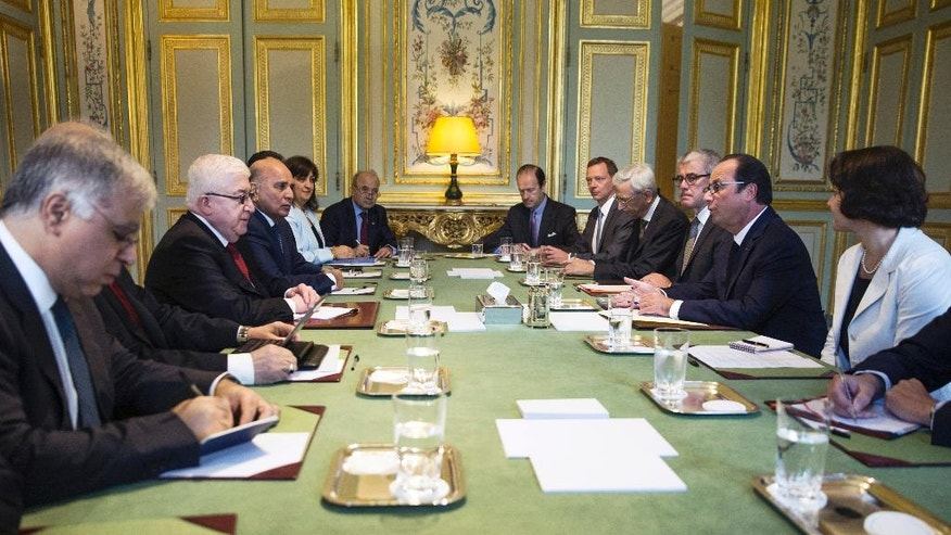 "French President Francois Hollande, second right, discusses with his Iraqi counterpart Fouad Massoum, second left, at the Elysee Palace in Paris, France, Monday, Sept. 15 2014. Reconnaissance planes at the ready, Hollande said there was ""no time to lose"" in the global push to combat extremists from the Islamic State group, minus the two countries who share most of Iraq's borders. (AP Photo/Etienne Laurent, Pool)"