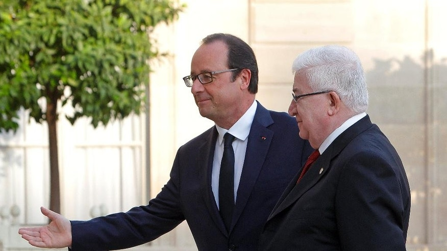 France's President Francois Hollande, left, welcomes his Iraqi counterpart Fouad Massoum, ahead of a conference with U.S. Secretary of State John Kerry and diplomats from around the world, at the Elysee Palace, in Paris, Monday, Sept. 15, 2014. (AP Photo/Thibault Camus)