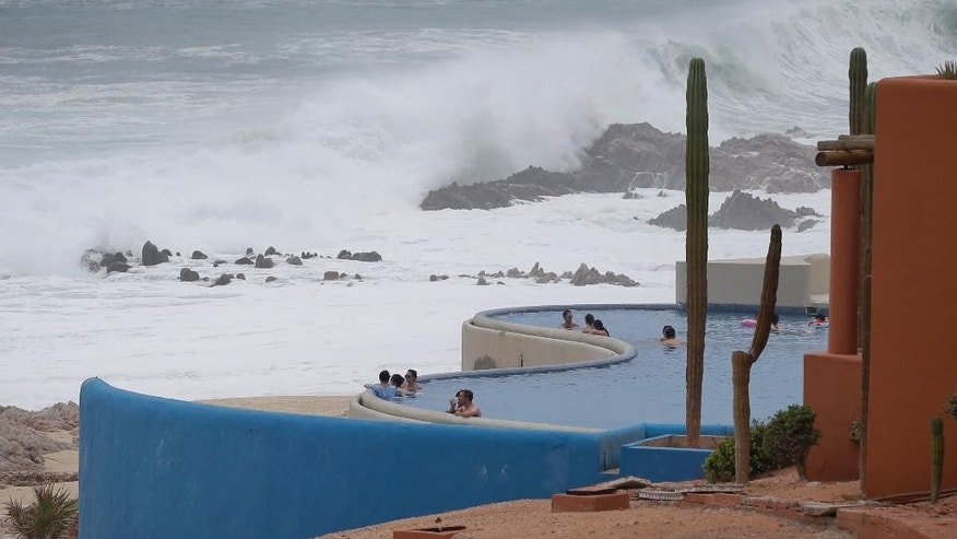 Tourists sit on the concrete stairs in the service area of a resort after the designated area for shelter was destroyed by winds in Los Cabos, Mexico,  Monday, Sept. 15, 2014. Hurricane Odile raked the Baja California Peninsula with strong winds and heavy rains early Monday as locals and tourists in the resort area of Los Cabos began to emerge from shelters and assess the damage. (AP Photo/Victor R. Caivano)