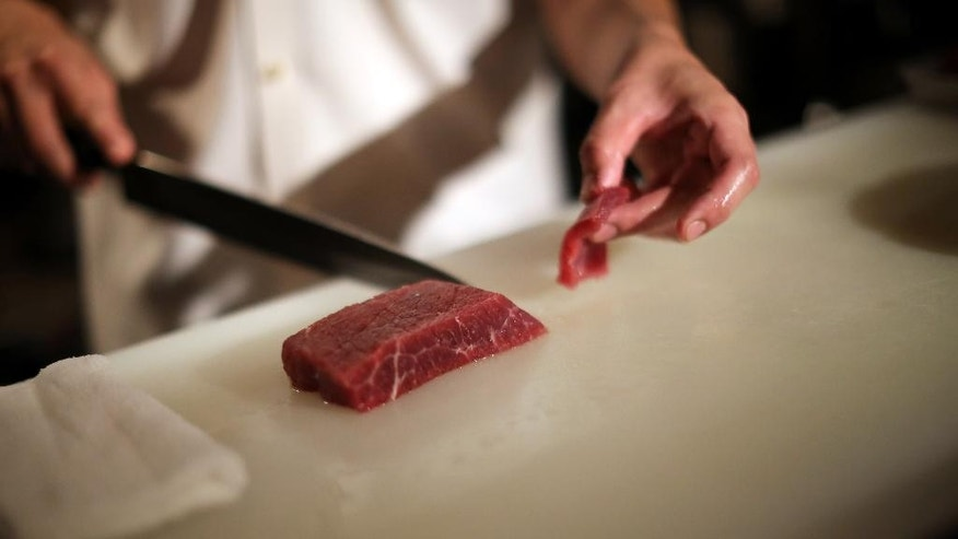 "In this Sept. 11, 2014 photo, chef of the Japanese restaurant ""COM FOR TABLE"" slices whale meat for a dish in in Tokyo. Whale meat continues to be one of the favorite dishes in this restaurant, but restaurant manager concerns about the future of its supply. At the International Whaling Commission meeting in Slovenia which opens Monday, Sept. 15, 2014, Japan is expected to seek international support for its plans to hunt minke whales in the Antarctic Ocean next year by scaling down the whaling research program the U.N. top court rejected earlier this year. The restaurant manager is hoping that supply will continue to sustain the demand for whale meat which has been a staple for the Japanese for such a long time. (AP Photo/Eugene Hoshiko)"