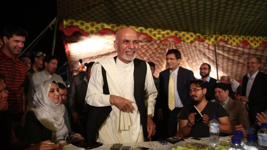 FILE - In this Wednesday, Sept. 10, 2014 file photo, Afghan presidential candidate and former Finance Minister Ashraf Ghani Ahmadzai, center, greets local and international journalists behind a dinner table after a news conference at his residence in Kabul, Afghanistan. The ballot counting in Afghanistan's five-month--long presidential election is finished, but as negotiations continue over the country's future political power structure, many here are asking: Does my vote even count? The two men now jockeying for presidential powers in secretive negotiations are Ahmadzai and former Foreign Minister Abdullah Abdullah. (AP Photo/Massoud Hossaini, File)