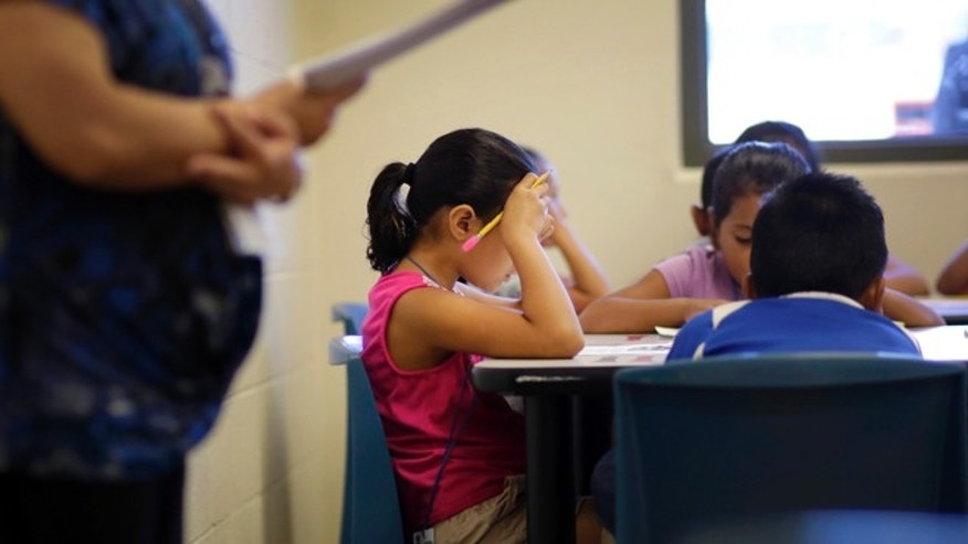 In this Wednesday, Sept. 10, 2014 photo, elementary aged children talk about a short story in Spanish during a class at the Karnes County Residential Center, a temporary home for immigrant women and children detained at the border in Karnes City, Texas. (AP Photo/Eric Gay)