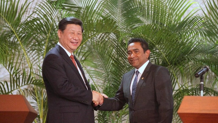 Chinese President Xi Jinping, left, shakes hands with Maldives President Yaamin Abdul Gayoom after joint statements at the latter's residence in Male, Maldives, Monday, Sept. 15, 2014. (AP Photo/Fayaz Moosa)