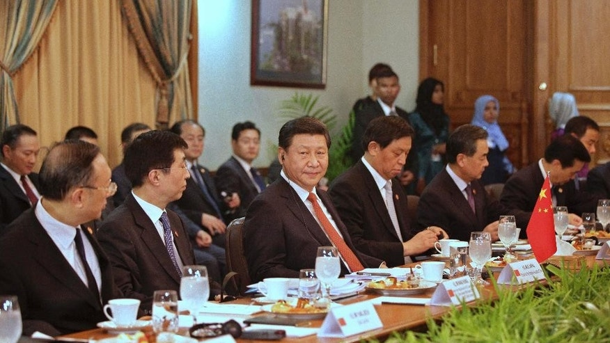 Chinese President Xi Jinping, center, sits with other members of the delegation during official talks with the Maldives government in Male, Maldives, Monday, Sept. 15, 2014. (AP Photo/Fayaz Moosa)