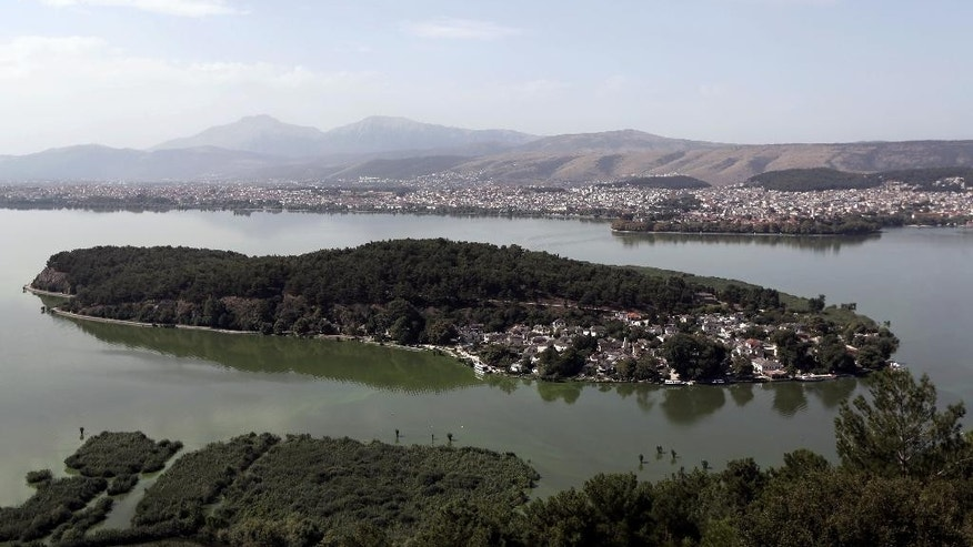 This Friday, Aug. 22, 2014, aerial photo shows a view of Pavmotis Lake, with the lake isle and city of Ioannina, in northwestern Greece. The country's severe financial crisis has forced businesses to seek fish exports in eastern Europe and promote the area as a day-trip destination. (AP Photo/Thanassis Stavrakis)