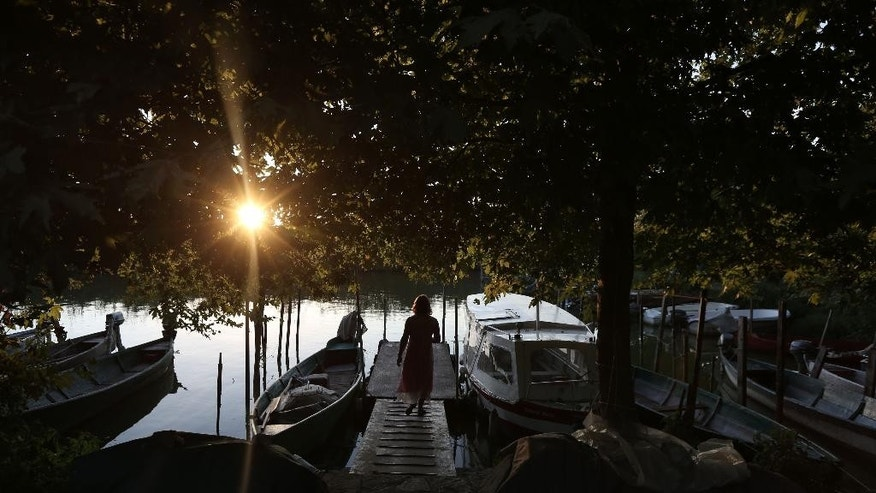 In this Saturday, Aug. 23, 2014, photo, fisherwoman Tasia Gini checks family boats during sunset on Nissaki (Islet) of Pamvotis Lake in Ioannina city, northwestern Greece. The country's severe financial crisis has forced businesses to seek fish exports in eastern Europe and promote the area as a day-trip destination. Local fishermen catch carp and eels. (AP Photo/Thanassis Stavrakis)