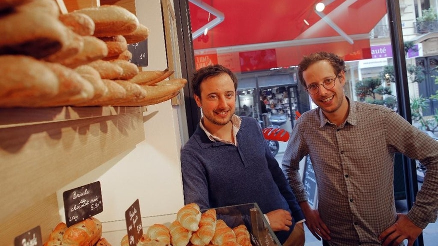 Brothers Jules, right and Emile Winocour pose in their bakery in Paris, Thursday, Sept. 11, 2014.  Marc Winocour and his two sons Jules and Emile  have enjoyed some success transforming the family farm into a field-to-table company that includes bread ovens, delivery trucks and a boutique. Revenues are climbing more than 50 percent a year. But even as customer interest grows, adding new employees to their team of 10 is a decision of last resort. For French business owners like them, the financial risk is too great and the government's promises to lighten the highest labor costs in the world and overhaul 3,000 pages of work rules are too remote. (AP Photo/Christophe Ena)