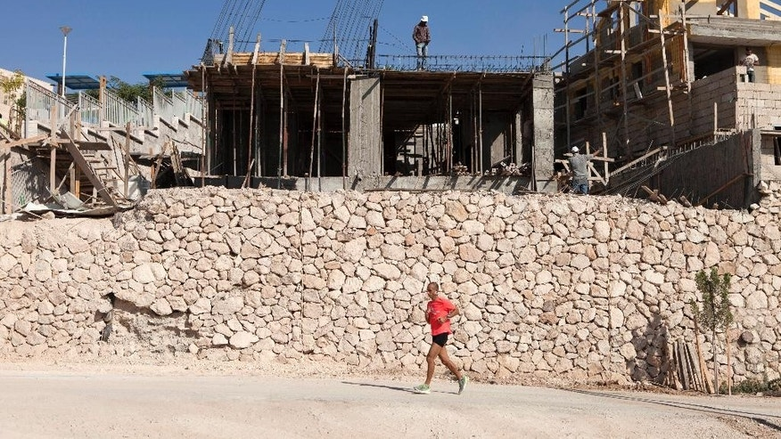 An Israeli Jogs past  Palestinians working at a construction site in the Jewish West Bank settlement of Maale Adumim, near Jerusalem. Tuesday, Sept. 16, 2014. Israel's settler population in the West Bank increased by 2 percent in the first half of the year, an advocacy group announced Tuesday, signaling robust growth in the settlements even while Israel was conducting peace talks with the Palestinians. The new figures drew criticism from the Palestinians, who seek the West Bank as part of a future state. The Palestinians and most of the international community consider Israeli construction there to be illegal or illegitimate. (AP Photo/Dan Balilty)