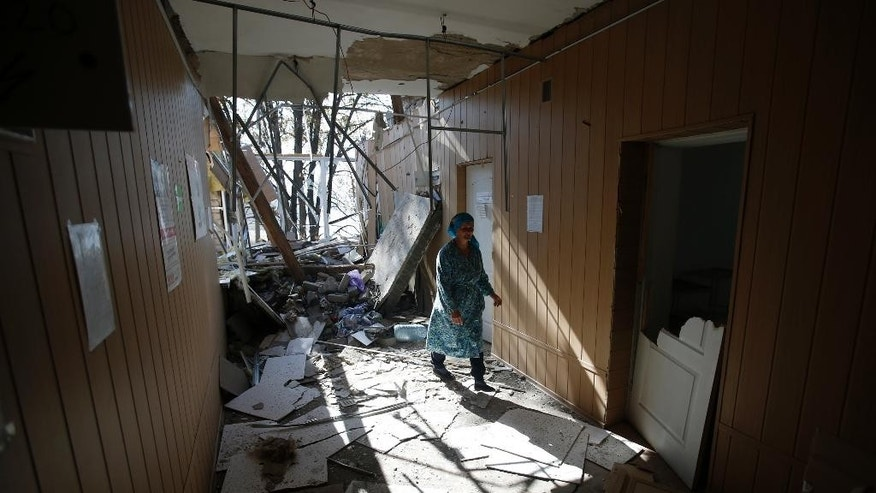 A woman shows the damage caused to a hospital in the village of Novosvitlivka, eastern Ukraine, Monday, Sept. 15, 2014. The village was severely damaged during fighting between government troops and the separatist rebels that eventually took control there in late August. (AP Photo/Darko Vojinovic)