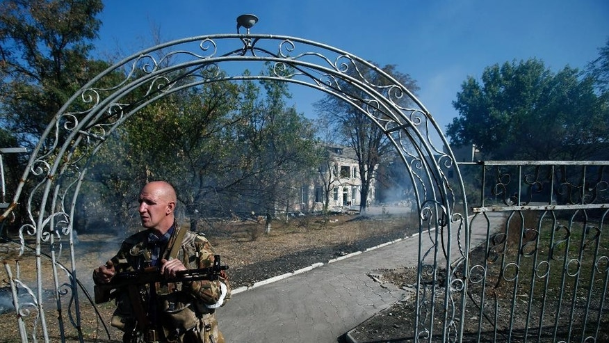 A pro-Russian gunman guards a damaged hospital in the village of Novosvitlivka, eastern Ukraine, Monday, Sept. 15, 2014. The village was severely damaged during fighting between government troops and the separatist rebels that eventually took control there in late August. (AP Photo/Darko Vojinovic)