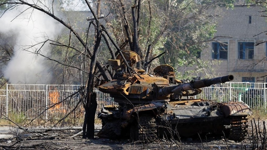 The remains of a charred tank in the village of Novosvitlivka, eastern Ukraine, Monday, Sept. 15, 2014. The village was severely damaged during fighting between government troops and the separatist rebels that eventually took control there in late August. (AP Photo/Darko Vojinovic)