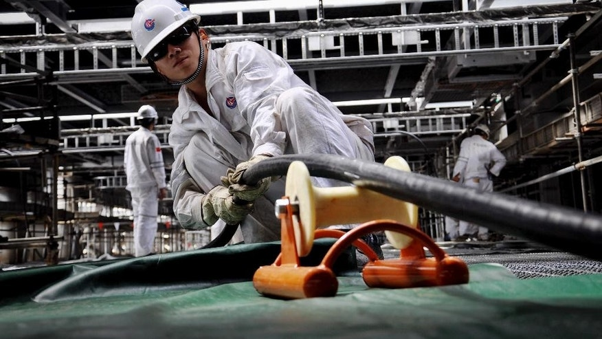 In this Sept. 11, 2014 photo, workers lay cables on a new oil rig under construction for China National Offshore Oil Corp. (CNOOC) in a shipyard in Qingdao in east China's Shandong province.  The Chinese exploration rig at the center of a tense maritime standoff with Vietnam earlier this year has made its first deep sea gas discovery in the politically volatile South China Sea, state media announced Tuesday, Sept. 16. The discovery by CNOOC was made about a month after its rig withdrew in July from Vietnam's exclusive economic zone to far less-contested waters closer to China. (AP Photo) CHINA OUT