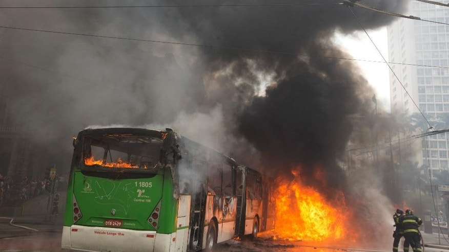 "Firefighters work to douse the flames of a bus set on fire by housing activists during an eviction in downtown Sao Paulo, Brazil, Tuesday, Sept. 16, 2014. Police and members of the so-called ""roofless"" movement are engaging in violent clashes after authorities evicted about 200 families from a building in Brazil's biggest city. (AP Photo/Andre Penner)"