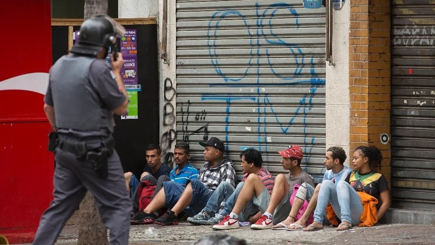 People who were evicted from a building are temporarily detained in order to collect their identification information, during an eviction operation in downtown Sao Paulo, Brazil, Tuesday, Sept. 16, 2014. The eviction of 200 families from the building led to violent clashes. Protesters set at least one bus ablaze while police fired rubber bullets, tear gas and stun grenades in an effort to disperse the crowd. (AP Photo/Andre Penner)