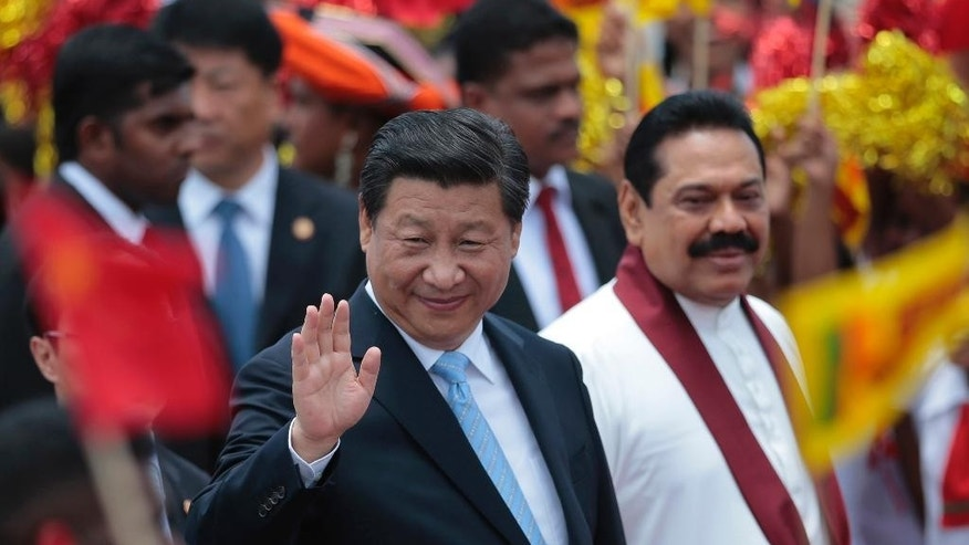 China's President Xi Jinping, left, waves as he walks with Sri Lankan President Mahinda Rajapaksa upon arrival at the airport in Colombo, Sri Lanka, Tuesday, Sept. 16, 2014. (AP Photo/Eranga Jayawardena)