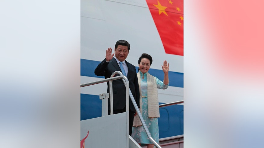 Chinese President Xi Jinping and his wife Peng Liyuan wave as they disembark from an airplane upon arrival at the airport in Colombo, Sri Lanka, Tuesday, Sept. 16, 2014. (AP Photo/Eranga Jayawardena)