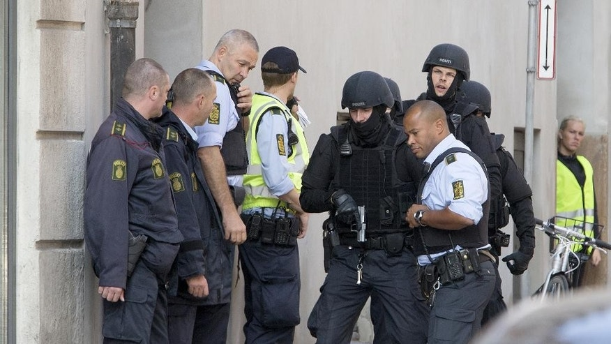 Police are seen outside Town Hall Square, Raadhuspladsen, in Copenhagen on Tuesday, Sept. 16, 2014. Police say shots have been fired inside a court building in the capital Copenhagen, killing one person and seriously wounding a second. In a statement Tuesday, police say a suspect has been arrested and a shotgun has been seized. There was no information on the victims or the suspect. The shooting happened just before 10 a.m. at the Bailiff's court, behind the city hall. (AP Photo/Finn Frandsen, POLFOTO) DENMARK OUT