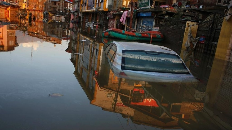 A car is partially submerged in an inundated neighborhood of Srinagar, Indian-controlled Kashmir, Monday, Sept. 15, 2014. Flooding from days of heavy monsoon rains partially submerged Srinagar and left more than 400 people dead in northern Pakistan and India. The flood waters have begun to recede, but vast fields of crops have been destroyed and tens of thousands of families have lost all their possessions. (AP Photo/ Altaf Qadri)