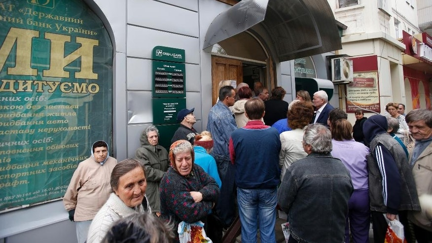 Residents of Donetsk line up in front of a bank in the town of Donetsk, eastern Ukraine, Tuesday, Sept. 16, 2014. The city council in Donetsk says three people have been killed and five wounded in shelling overnight in the city in eastern Ukraine. The casualties come as Ukraine's parliament plans to review a bill that would give greater autonomy to the eastern regions of Donetsk and Luhansk, where fighting between separatists and Kiev's forces has claimed at least 3,000 civilian lives. (AP Photo/Darko Vojinovic)