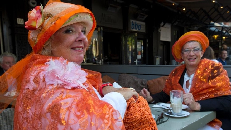 "Pauline de Haas, left, and Jetty Duijndam, right, dressed in the colors of the Royal House of Orange, enjoy a coffee on a terrace in The Hague, Netherlands, Tuesday, Sept. 16, 2014, as they wait for the parade of the Golden Carriage carrying Netherlands' King Willem-Alexander to the 13th century ""Hall of Knight"" where he officially open the new parliamentary year with a speech outlining the government's plan and budget policies for the year ahead. (AP Photo/Peter Dejong)"