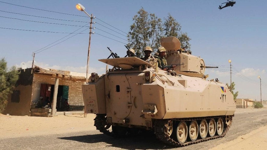 FILE - In this Tuesday, May 21, 2013, file photo, Egyptian Army soldiers patrol in an armored vehicle backed by a helicopter gunship during a sweep through villages in Sheikh Zuweyid, northern Sinai, Egypt. and police facilities and checkpoints. A powerful explosion killed several Egyptian police conscripts and an officer near the border town of Rafah in the restive Sinai Peninsula early Tuesday, Sept. 16, 2014, in an attack that bore the hallmarks of a local al-Qaida-inspired group, Egyptian security officials said. The Interior Ministry and a security official said the bomb was hidden deep under the asphalt of a highway, in an area called Wadi Halfa, where a joint police and army force was passing early in the morning. (AP Photo, File)