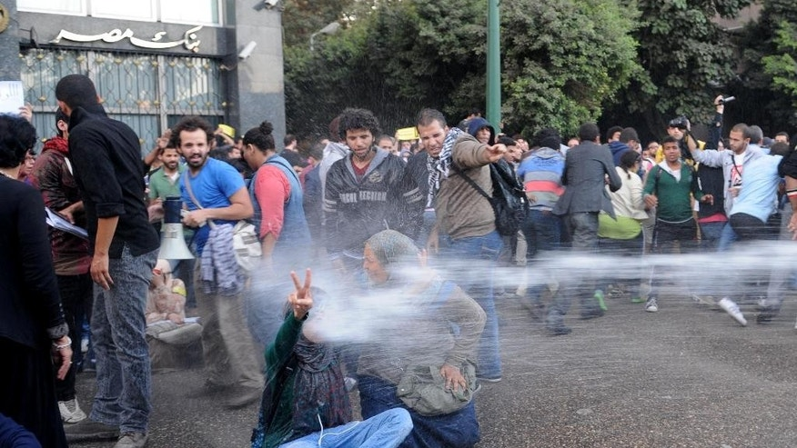FILE -- In this Tuesday, Nov. 26, 2013 file photo, Egyptian police fire water cannons to disperse a protest by secular anti-government activists in Cairo. Mahmoud Abdel-Bari, the spokesman of Egypt's transitional justice ministry, says the body is drafting amendments to the country's disputed protest law, which bans demonstrations without a police permit. Abdel-Bari said Tuesday that the ministry will announce a draft law within days saying amendments could include lighter penalties and changes in procedures related to obtaining permits from police for protests. (AP Photo/Mohammed Asad, File)