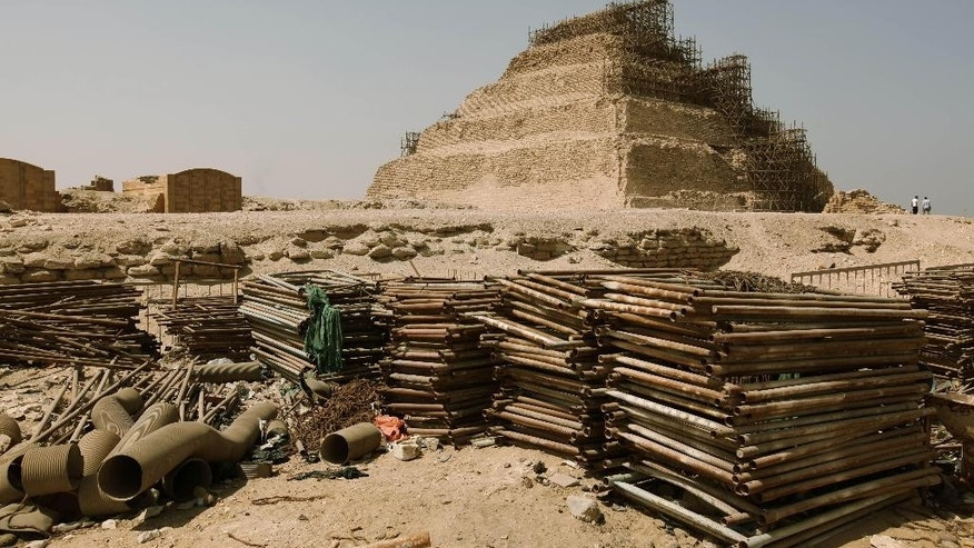 Building materials gather dust at the foot of the Djoser Pyramid in Saqqara, Egypt, Tuesday, Sept. 16, 2014. The restoration of the 4,600-year old pyramid has prompted controversy between the Ministry of Antiquities, activists and archaeologists including the new brick work at the base of the pyramid. (AP Photo/Samuel McNeil)