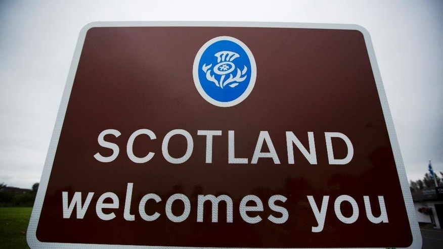 "A ""Scotland welcomes you"" sign stands beside a road near Gretna, Scotland, Monday, Sept. 15, 2014.  If Scottish-based voters approve separation from the U.K. on Thursday, officials from Scotland and Britain will have to sort out assets and debt, questions over continued membership in the United Nations and European Union, and whether to retain a common currency.  (AP Photo/Matt Dunham)"