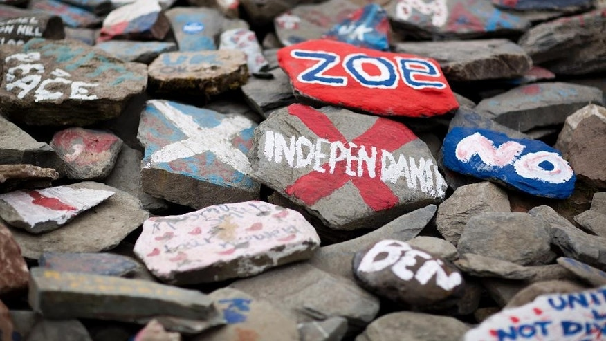 "Decorated stones form ""The Auld Acquaintance"" cairn, which is being built as a monument supporting the union of Scotland and the U.K. on the England Scotland border near Gretna, Scotland, Monday, Sept. 15, 2014.  The stone circle is being built as a mass participation project as a monument to togetherness, open to anyone who wishes to place a stone there, decorated or otherwise.  If Scottish-based voters approve separation from the U.K. on Thursday, officials from Scotland and Britain will have to sort out assets and debt, questions over continued membership in the United Nations and European Union, and whether to retain a common currency.  (AP Photo/Matt Dunham)"