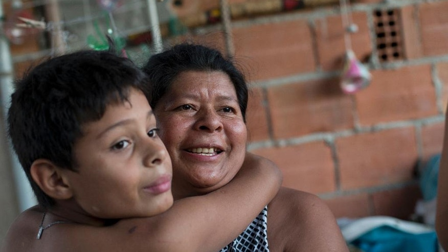 In this Aug. 24, 2014, photo, Wesly, 16, embraces his mother Twry Pataxo, 46, from the Pataxo tribe, at their home, in the Mare slum in Rio de Janeiro, Brazil, Sunday, Aug. 24, 2014. Born and raised in an indigenous community in the northeastern state of Bahia, Twry Pataxo has called the Mare slum, one of Rio's most violent, her home since arriving in the city 15 years ago. (AP Photo/Silvia Izquierdo)
