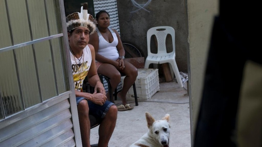 In this Aug. 24, 2014 photo, Afonso Xamakiri, left, wearing an indian head dress, watches a soccer game on a television set at the Mare slum in Rio de Janeiro, Brazil.  Accelerating deforestation, as well as frequent and sometimes deadly land conflicts with loggers, miners and farmers, are pushing indigenous people into the slums. Recently the Brazilian government said deforestation of the Amazon rain forest region, where a third of Brazil's indigenous people are concentrated, was up 29 percent last year, compared with a year earlier. (AP Photo/Silvia Izquierdo)