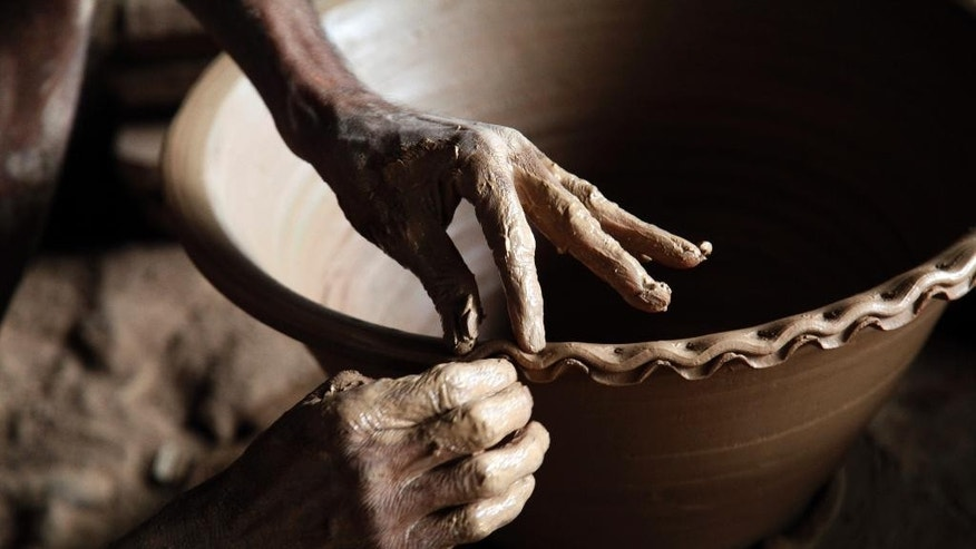 In this photo taken on Aug. 29, 2014, a man puts a decorative edge on a clay flower pot in Twante township, southwest of Yangon, Myanmar. For generations, the Myanmar town of Twante has been known for its thriving pottery industry. Even today, residents can be seen sitting on wooden stools beneath the thatched roofs of their homes, placing lumps of soft clay onto wheels and shaping it with the gentle press of their fingertips into pots for cooking, storing water, preserving fish or flowers.  (AP Photo/Khin Maung Win)