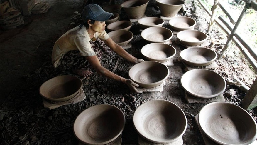 In this Aug. 29, 2014 photo, a woman arranges earthen pots to get dry under the sun at a workshop in Twante, southwest of Yangon, Myanmar. For generations, the Myanmar town of Twante has been known for its thriving pottery industry. Even today, residents can be seen sitting on wooden stools beneath the thatched roofs of their homes, placing lumps of soft clay onto wheels and shaping it with the gentle press of their fingertips into pots for cooking, storing water, preserving fish or flowers. (AP Photo/Khin Maung Win)