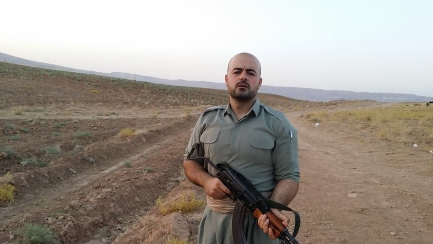 """In this image provided by Shaho Pirani shows  Shaho Pirani posing with an automantic weapon near the village of Koya in Iraqi Kurdistan in June 2014. The Iranian Kurd living in Denmark, was on a month-long training camp for the Kurdish diaspora organized by Iranian branch of the Kurdistan Democratic Party. He joined Kurds from Norway, Switzerland and Britain for a crash-course on politics followed by weapons training. Shaho Pirani says he's just a phone call away from leaving his quiet life in Denmark and joining Kurdish forces battling against Islamic State militants in Iraq. The 30-year-old Kurd, who fled from Iran with his older brother in 1991, says he feels a moral duty to help the Peshmerga, the armed forces of the Kurdistan Regional Government, to fight the """"psychopaths"""" of the IS group. (AP Photo/Shaho Pirani)"""