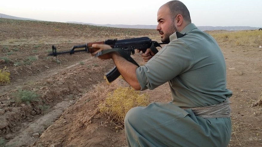 """In this image provided by Shaho Pirani ,  Shaho Pirani shoots with an automantic weapon near the village of Koya in Iraqi Kurdistan in June 2014. The Iranian Kurd living in Denmark, was on a month-long training camp for the Kurdish diaspora organized by Iranian branch of the Kurdistan Democratic Party. He joined Kurds from Norway, Switzerland and Britain for a crash-course on politics followed by weapons training. Shaho Pirani says he's just a phone call away from leaving his quiet life in Denmark and joining Kurdish forces battling against Islamic State militants in Iraq. The 30-year-old Kurd, who fled from Iran with his older brother in 1991, says he feels a moral duty to help the Peshmerga, the armed forces of the Kurdistan Regional Government, to fight the """"psychopaths"""" of the IS group. (AP Photo/Shaho Pirani)"""