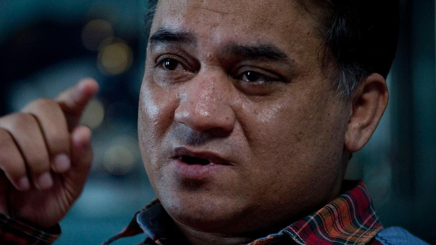In this Feb. 4, 2013 photo, Ilham Tohti, an outspoken scholar of China's Turkic Uighur ethnic minority, speaks during an interview at his home in Beijing, China. Tohti was set to go on trial on Wednesday, Sept. 17, 2014 on separatism charges in the country's far western region of Xinjiang. (AP Photo/Andy Wong)