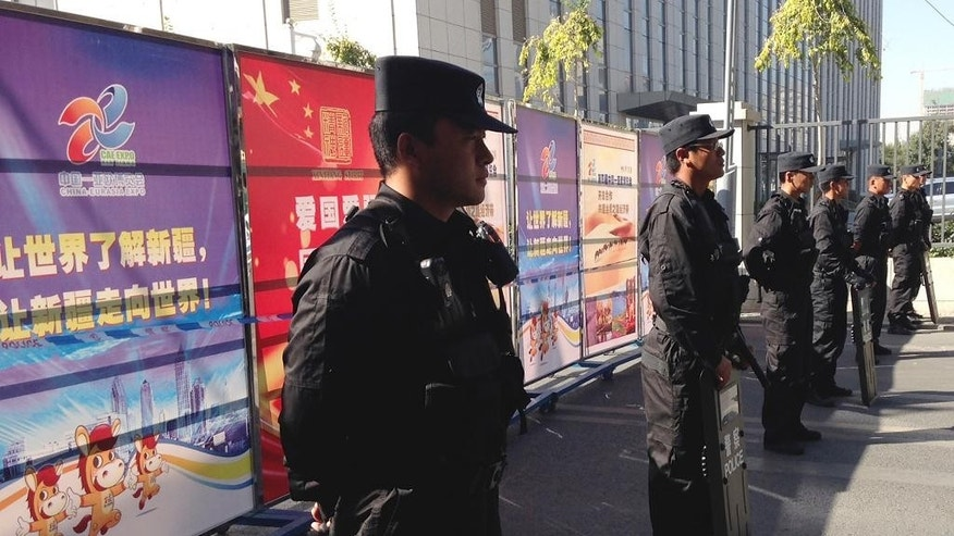 Armed policemen stand guard near Xinjiang's tourism advertisement boards, which authority used to block off the road heading to Urumqi People's Intermediate Court in Urumqi, China's northwestern region of Xinjiang Wednesday, Sept. 17, 2014. Ilham Tohti, a scholar from China's Muslim Uighur minority community who often criticized the country's ethnic policies is set to go on trial on separatism charges in the country's far western region of Xinjiang. (AP Photo/Jack Chang)