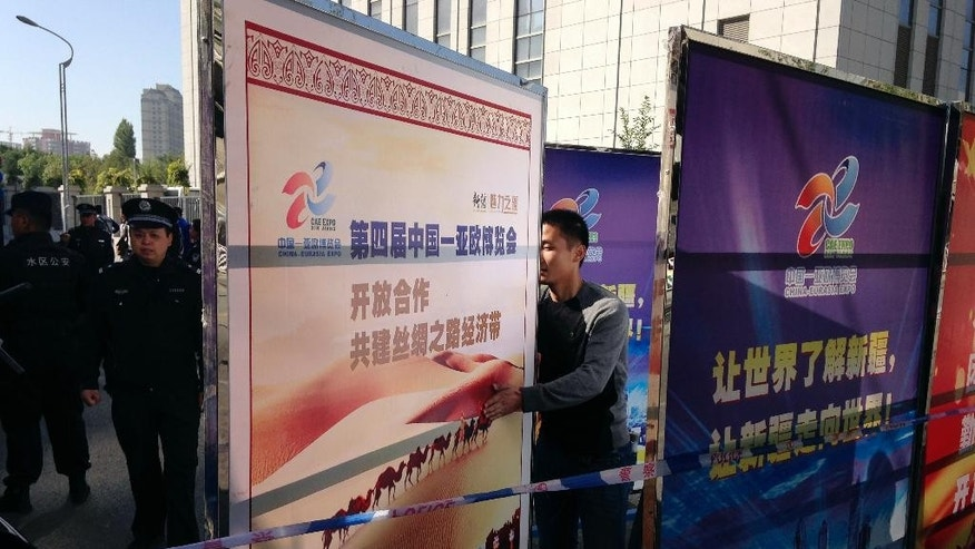 A plain clothes policeman arranges a Xinjiang's tourism advertisement board to block off the road heading to Urumqi People's Intermediate Court in Urumqi, China's northwestern region of Xinjiang Wednesday, Sept. 17, 2014. Ilham Tohti, a scholar from China's Muslim Uighur minority community who often criticized the country's ethnic policies is set to go on trial on separatism charges in the country's far western region of Xinjiang. (AP Photo/Jack Chang)