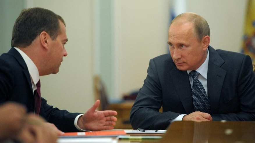 Russian President Vladimir Putin listens to Russian Prime Minister Dmitry Medvedev, left, during the Security Council meeting in the Novo-Ogaryovo residence, outside Moscow, Russia, Monday, Sept. 15, 2014.(AP Photo/RIA Novosti, Alexei Druzhinin, Presidential Press Service)