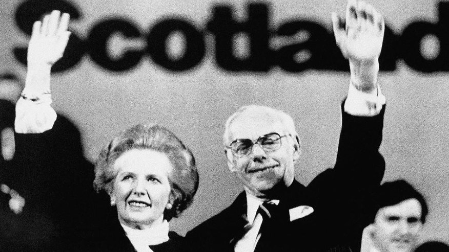 FILE -This is a Friday, May 16, 1987 file photo of  the then British Prime Minister Margaret Thatcher and her husband Denis as they wave to the audience after her speech at the Scottish Conservative conference  in Perth, Scotland. Thatcher has launched her general election campaign by promising more popular capitalism. With the Thursday Sept 18, 2014 referendum looming, proponents of Scottish independence are using one of the main weapons in their armory _ Scotland's widespread mistrust of the Conservative Party. The Conservatives' drop in support in Scotland can be largely traced back to 1979, when Margaret Thatcher won the general election and began 18 years of Tory rule. Successive Conservative governments introduced policies to turn around Britain's economic fortunes, to reduce the role of the state and allow private enterprise to flourish.  (AP Photo/John Redman, File)