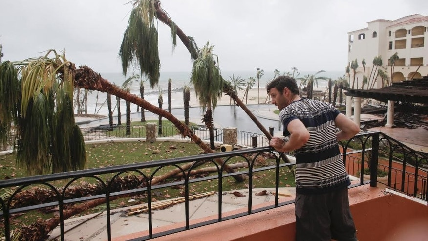 Tourist Patrick Egan from California looks at the interior patios of the Hilton hotel, damaged by Hurricane Odile in Los Cabos, Mexico, Monday, Sept. 15, 2014. Hurricane Odile blazed a trail of destruction through Mexico's Baja California Peninsula that leveled everything from ramshackle homes to big box stores and luxury hotels, leaving roads and entire neighborhoods as disaster zones. (AP Photo/Victor R. Caivano)