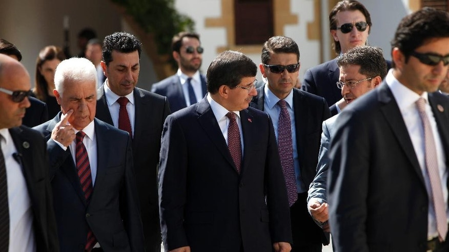 Turkey's Prime Minister Ahmet Davutoglu, center, and Turkish Cypriot leader Dervis Eroglu, second left, walk surrounded by the security after a meeting in the breakaway Turkish Cypriot north of ethnically divided Cyprus on Tuesday, Sept.16, 2014. Turkey's new prime minister strongly rejected Western media reports that many of his fellow countrymen are swelling the ranks of the Islamic State group. Davutoglu says there's many more Europeans signing up with the extremist group than there are Turks. Cyprus was divided in 1974 when Turkey invaded after a coup by supporters of union with Greece. A Turkish Cypriot Declaration of Independence is recognized only by Turkey which maintains 35,000 troops there. (AP Photo/Petros Karadjias)