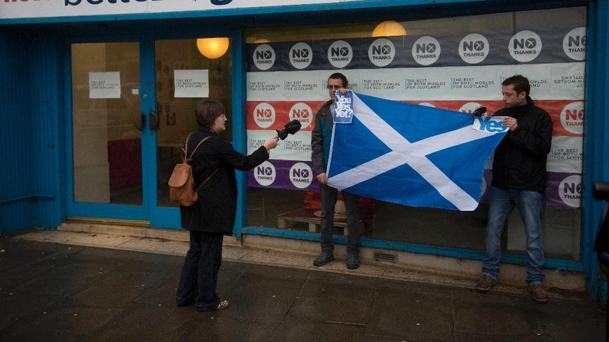 "A passerby argues with two Scottish independence referendum 'Yes' supporters holding a Scottish Saltire flag outside the ""Better Together"" No campaign offices in Edinburgh, Scotland, Monday, Sept. 15, 2014.  If Scottish voters this week say Yes to independence, not only will they tear up the map of Great Britain, they'll shake the twin pillars of Western Europe's postwar prosperity and security — the European Union and the U.S.-led NATO defense alliance.  (AP Photo/Matt Dunham)"