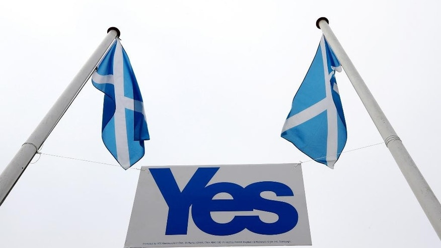 "A pair of Saltire's fly above a Yes sign in Eyemouth, Scotland, Tueday, Sept. 16, 2014. The two sides in Scotland's independence debate are scrambling to convert undecided voters, with just two days to go until a referendum on separation. Anti-independence campaigners are pushing home their message that a ""No"" vote doesn't mean the status quo. The three main British political parties are promising Scotland greater powers, including tax-raising authority, if it remains part of the United Kingdom. The Yes campaign says the promises are vague and reveal the No side's desperation, with polls suggesting the outcome will be close. Scottish Deputy First Minister Nicola Sturgeon said ""the only way to guarantee the real powers we need in Scotland is to vote Yes."" (AP Photo/Scott Heppell)"