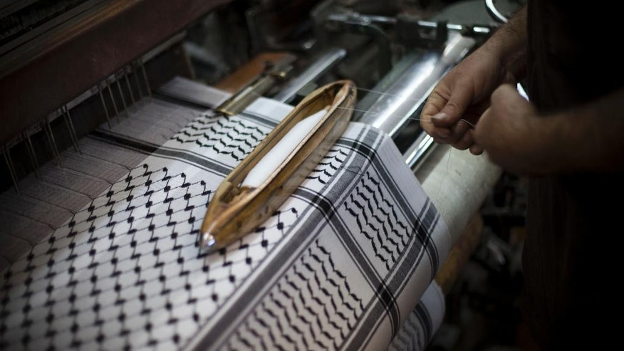 FILE - In this Wednesday, July 13, 2011 file photo, a Palestinian worker in a family owned workshop that makes checkered head scarves, or keffiyehs, works a loom, in the West Bank city of Hebron. The Palestinian economy is expected to contract for the first time in seven years in 2014, shrinking by 4 percent, the result of the recent Gaza war, continued Israeli and Egyptian restrictions on Palestinian trade and a drop in foreign aid, the World Bank said Tuesday. The bank issued the report ahead of a meeting next week of donor nations to the Palestinians on the sidelines of the U.N. General Assembly. (AP Photo/Bernat Armangue, File)