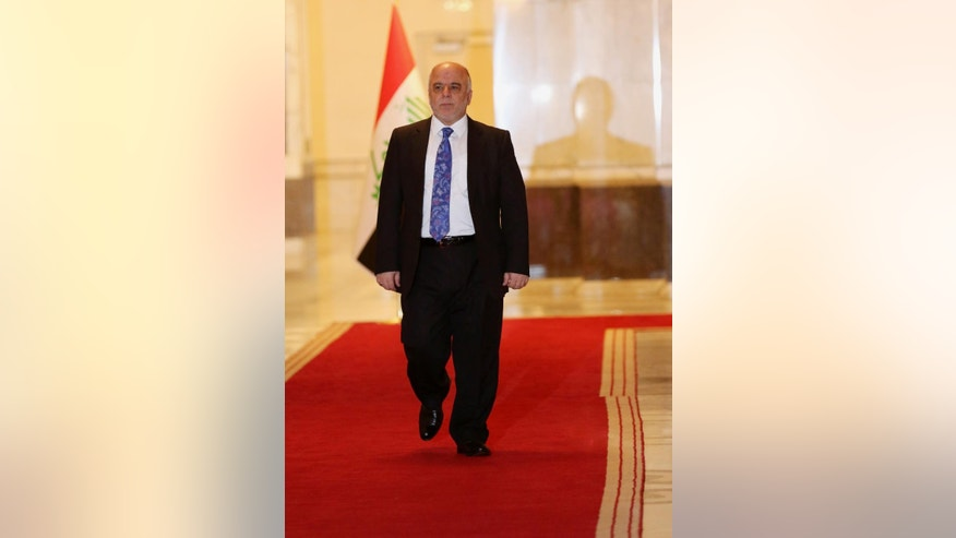 Iraq's Prime Minister Haider al-Abadi walks to an interview with The Associated Press in Baghdad, Iraq, Wednesday, Sept. 17, 2014. Iraq's new prime minister says foreign ground troops are neither necessary nor wanted in his country's fight against the Islamic State group. (AP Photo/Hadi Mizban)