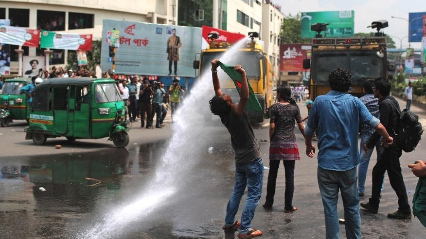 "A Bangladeshi holds high his national flag as police use a water cannon to break up a protest against a court ruling commuting the death sentence of Jamaat-e-Islami leader Delwar Hossain Sayedee, in Dhaka, Bangladesh, Wednesday, Sept. 17, 2014. Sayedee must remain in prison ""for the rest of his natural life,"" Chief Justice Muzammel Hossain said. A war crimes tribunal convicted the Islamist political leader in February 2013 for eight counts involving mass killings, rape and atrocities committed during the nine-month war against Pakistan in 1971. (AP Photo/A.M. Ahad)"